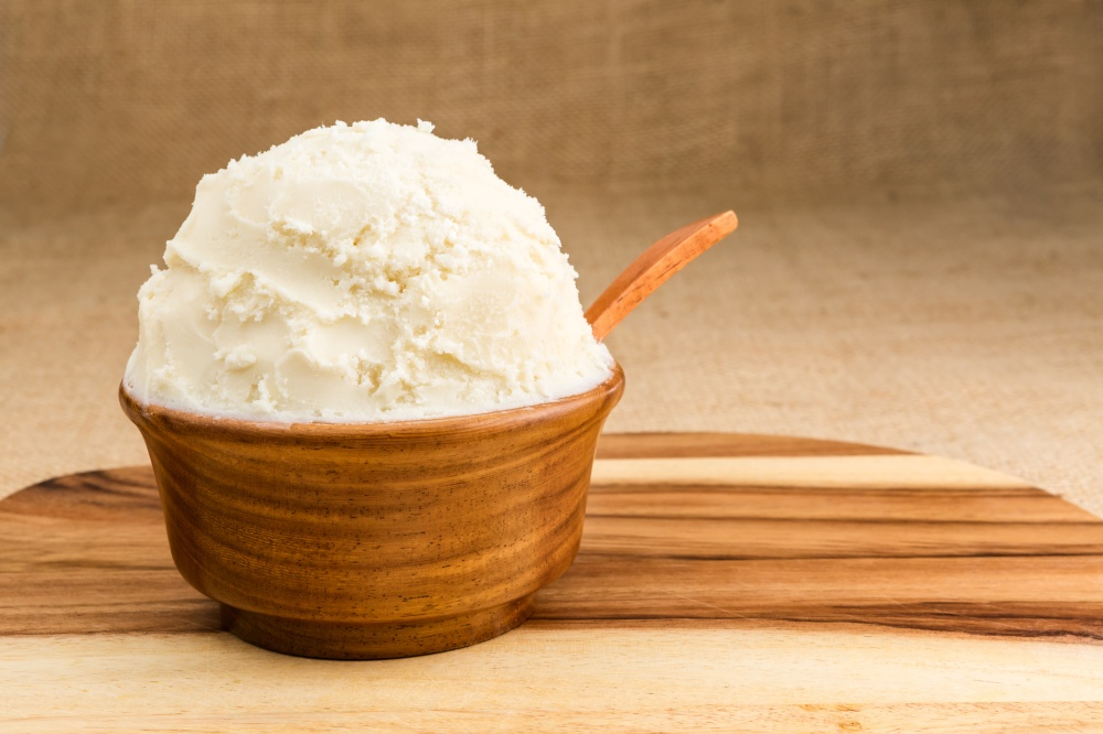 Unrefined, organic Shea butter in the wooden bowl with the spoon, stands on the wooden board, jute fabric background.